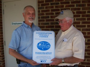Charlie Wootton presents Jack Boswell with a Conservation Friendly sign for his farm.